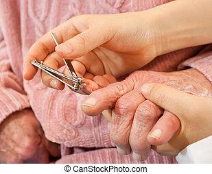 Helping senior cutting nail