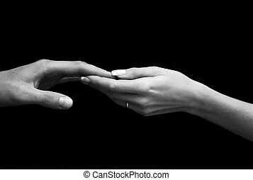 Helping - Man\\\'s and female hand on a black background