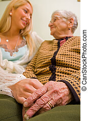 An old woman holding a younger person's hand (that could be a granddaughter, social worker; focus on hands) - part of a series.
