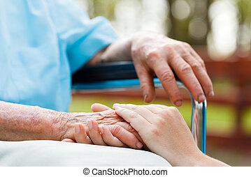 Holding elderly lady's hands sitting in wheelchair.