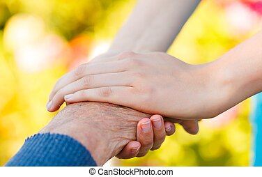 Young hand holding an elderly man's hand - conceptual picture.