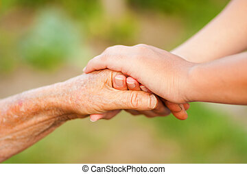 Young holding hand of an elderly woman outdoors.
