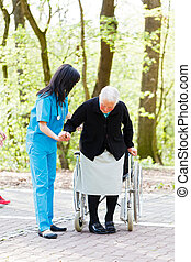 Helping to sit down - Caring nurse or doctor helping senior ...