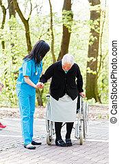 Helping to sit down - Caring nurse or doctor helping senior...