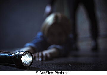 Helpless female victim reaching out to a flashlight