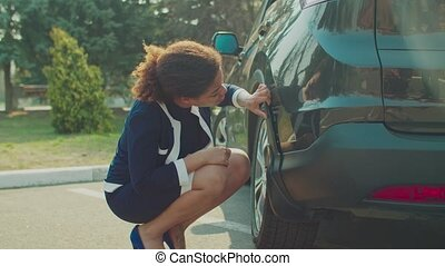 Frustrated worried african american female driver checking car scratches and dents after road accident. Unhappy black woman looking at damaged scratched vehicle outdoors, being helpless and upset.