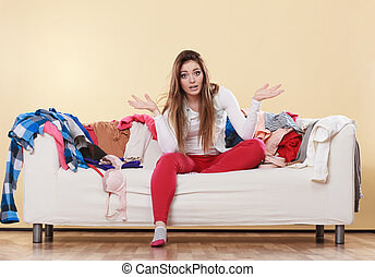 Helpless woman sitting on sofa in messy room home.