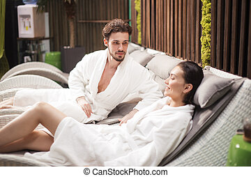 pleasant unshaven man looking at relaxing girlfriend in the spa center