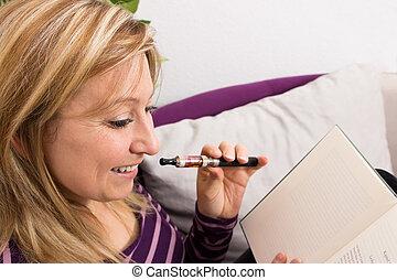 hembra, con, e-cigarette, y, un, libro