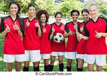 hembra, equipo de fútbol, el gesticular, pulgares arriba, en, parque