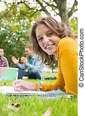 hembra, notas de letra, con, estudiantes, usar la computadora portátil, en el estacionamiento