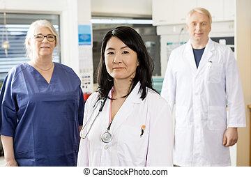 hembra, profesional médico, posición, con, equipo