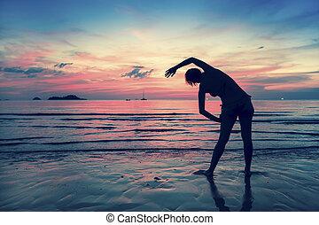 hembra, silueta, hacer, ejercicios, en, el, océano, playa, en, ocaso, time.