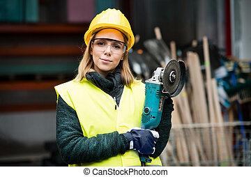 hembra, trabajador, con, ángulo, amoladora, en, un, warehouse.