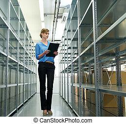 hembra, trabajador, con, portapapeles, oraganizing, inventario, y, acción, en, almacén