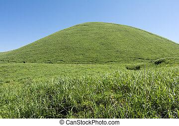 Green hemispherical hill in the grassy plain under blue sky