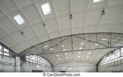 Hemispherical reinforced concrete load bearing roof with windows in huge industrial warehouse. White interior. Unique soviet architecture.