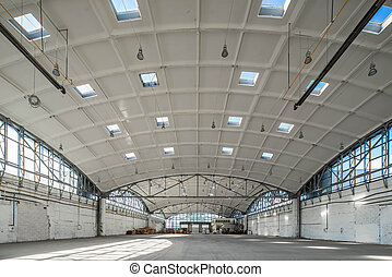 Huge industrial warehouse. Modern interior. Unique architecture. Hemispherical reinforced concrete load bearing roof. Stack wooden pallets.