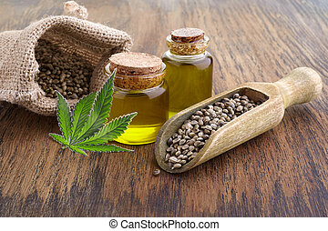 hemp seed in wooden spoon, oil in glass jar, green leaves cannabis on wooden background