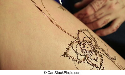 Henna body painting. View of process, close-up