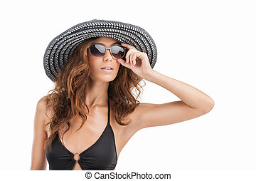 Her brand new sunglasses. Portrait of attractive young women in swim wear and hat looking away while standing isolated on white