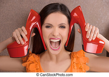 Her favorite shoes. Excited young woman holding red heeled...