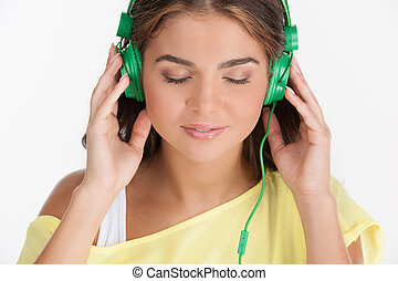 Her favourite music. Beautiful young woman listening to the music and keeping her eyes closed while isolated on white