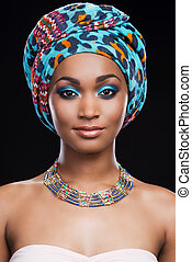 Her perfection in her style. Beautiful African woman wearing headscarf and necklace looking at camera while standing against black background