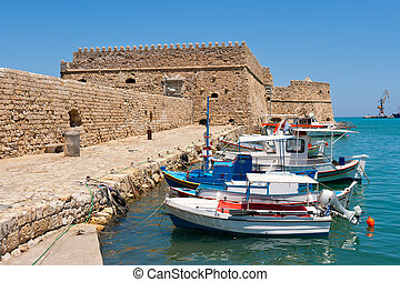 Fishing boats and Venetian Fortress in Heraklion harbour. Crete, Greece
