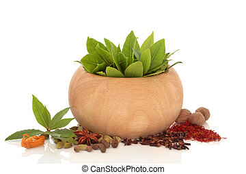 Bay leaf herb in a beech wood bowl with mixed spice of saffron, nutmeg, star anise, cardamom, and mace, isolated over white background with reflection.
