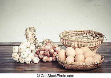 Herb ingredients,  onion, garlic and eggs on dark wood table
