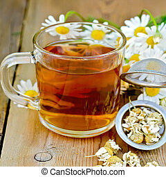 Herbal chamomile tea in a mug with strainer on the board - ...