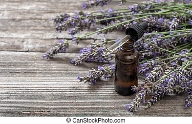 Herbal oil and lavender flowers bouquet on wooden background
