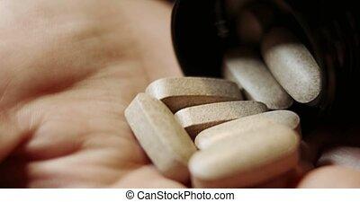 Herbal pills on senior woman palm.