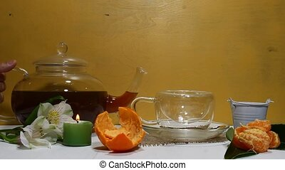 Herbal tea - A glass tea kettle pouring black tea in a...