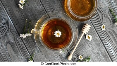 Herbal tea and jar of honey - Top view of glass mug with...