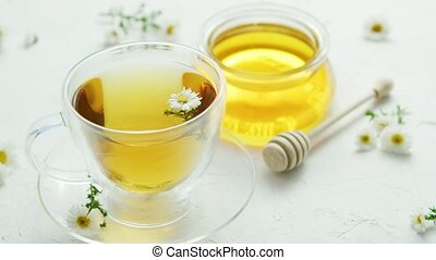 Herbal tea and jar of honey - Transparent glass cup with...
