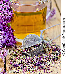 Herbal tea from oregano with strainer in glass mug