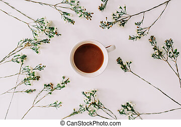 Herbal tea in a frame of flowers and branches on white background. Flat lay, top view, copy space.