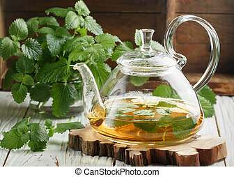 Herbal tea in a transparent teapot on the table and sprigs ...