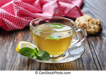 Herbal tea in cup with mint and lemon on wooden background