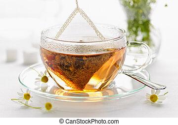 Glass teacup with soothing herbal tea in silk bag