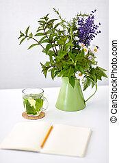 herbal tea, notebook and flowers in jug on table