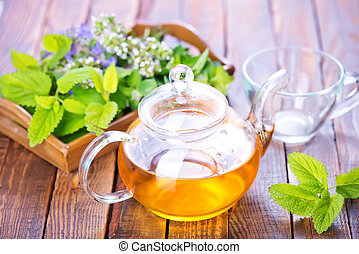 herbal tea - fresh herb and herbal tea on a table