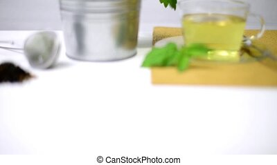 Herbal tea with melissa in a glass cup a green napkin on a ...
