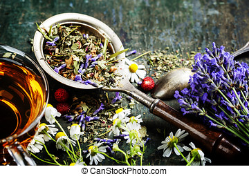 Herbal tea with wild flowers and berry on wooden background...