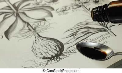 herbal tincture - drops of a herbal tincture falling on a...
