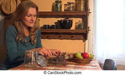 herbalist girl put oregano in glass. Ancient rural room. 4K