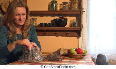 Herbalist woman put dried marjoram herbs on wooden shelf. 4K