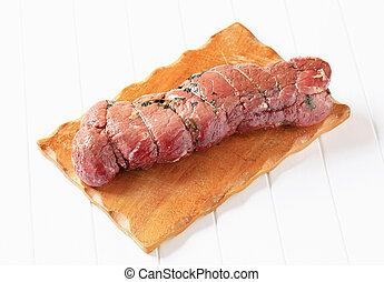 Herbed beef tenderloin on cutting board